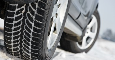 Car with winter tyres installed on light alloy wheels in snowy o